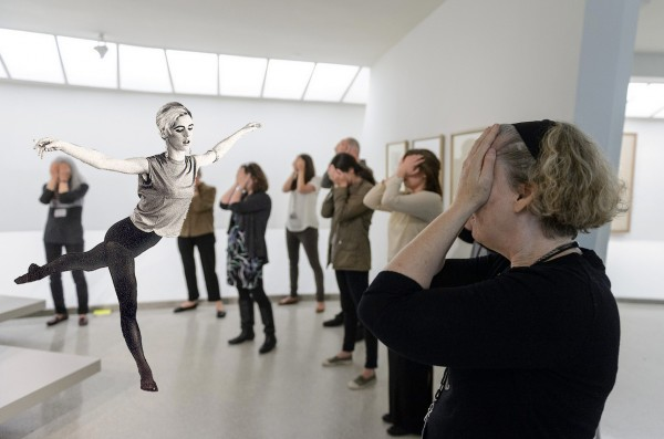 "photo of Edie Sedgwick performing her ""Mylar Ballerinas"" work at the Guggenheim museum in New York. In the image we see participants in a gallery with their hands covering their eyes as Sedgwick dances and performs an arabesque. In this work Sedgwick tries to move air molecules giving her audience a non-visual, haptic experience of her performance."