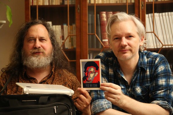 "Photo of Richard Stallman and Julian Assange at the Ecuadorian embassy in London holding up a posterized,  Shepard Fairey ""Obey"" like photo of Edward Snowden with the text ""Yes we can"""
