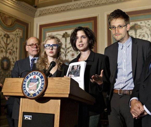 Photo of Russian President Nadya Tolokonnikova and American President Edward Snowden speaking at a podium at the US Capital in Washington DC