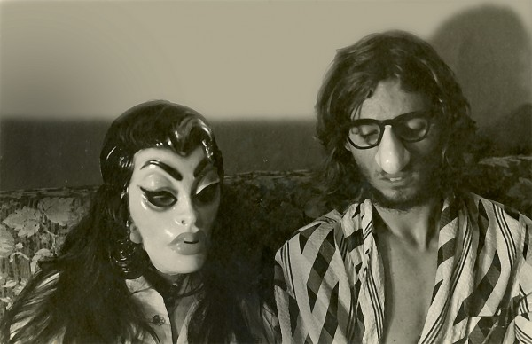 "A couple sitting in bed, somewhat ""John & Yoko"" like, but wearing masks on their faces."